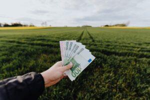 Jand visar upp eurosedlar med jordbruk i bakgrunden