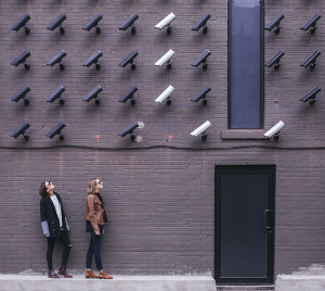 Two women looking up at an array of surveillance cameras