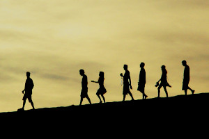 Silhuettes of people walking downhill